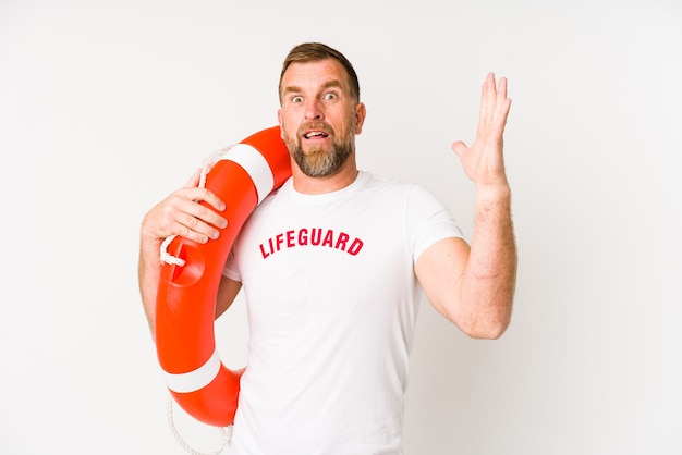 Senior badmeester man geïsoleerd op een witte achtergrond een aangename verrassing ontvangen, opgewonden en handen opheffen.