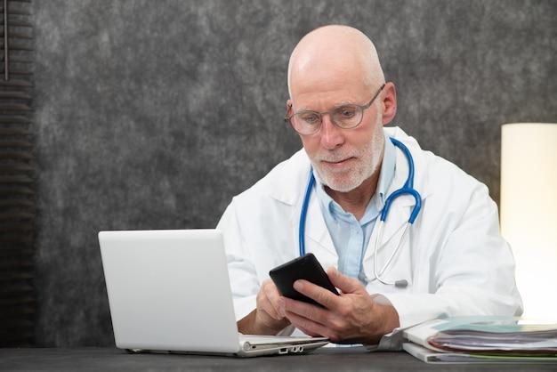 Senior bebaarde dokter lezen bericht op telefoon