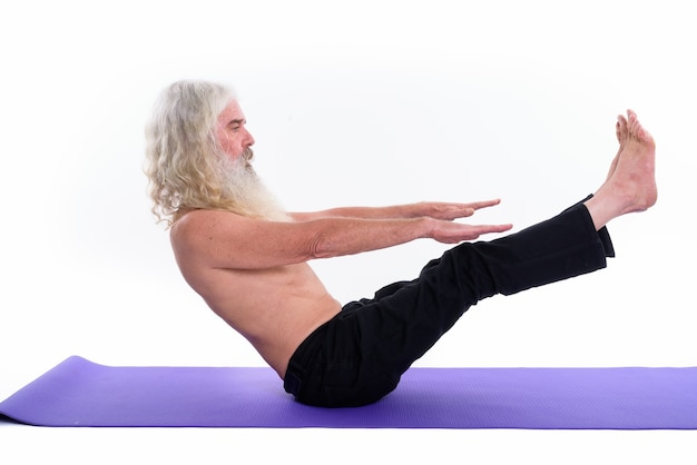 Senior bebaarde goeroe man doet yoga houdingen en stretching