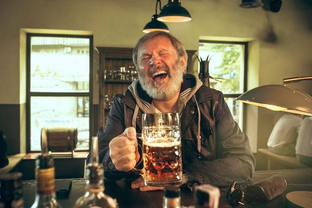 Senior bebaarde man alcohol drinken in pub en kijken naar een sportprogramma op tv. genieten van mijn favoriete krieltjes en bier. man met mok bier aan tafel zitten. voetbal- of sportfan. menselijke emoties concept