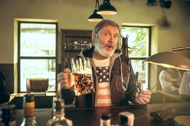 Senior bebaarde man alcohol drinken in pub en kijken naar een sportprogramma op tv. genieten van mijn favoriete krieltjes en bier.