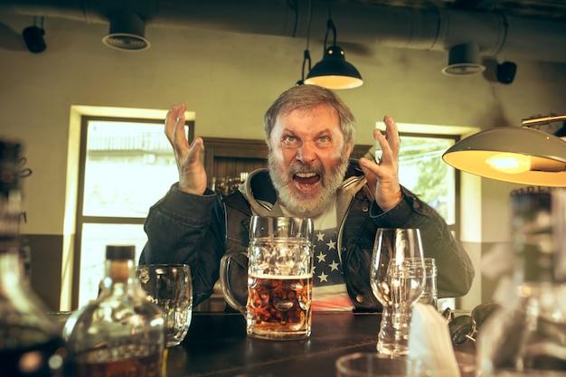 Senior bebaarde man alcohol drinken in pub en kijken naar een sportprogramma op tv.