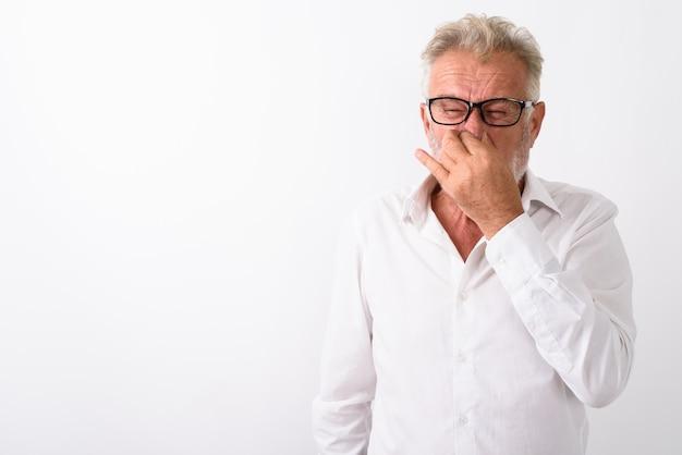 Senior bebaarde man die neus bedekt en walgt terwijl hij een bril op wit draagt