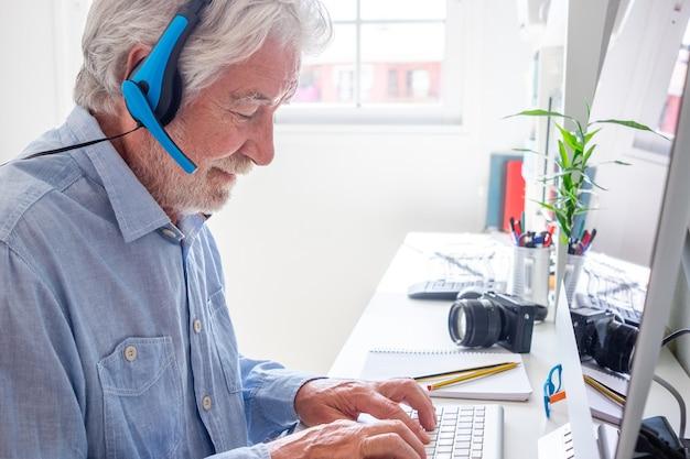 Senior bebaarde man met koptelefoon typen op toetsenbord vanuit kantoor aan huis