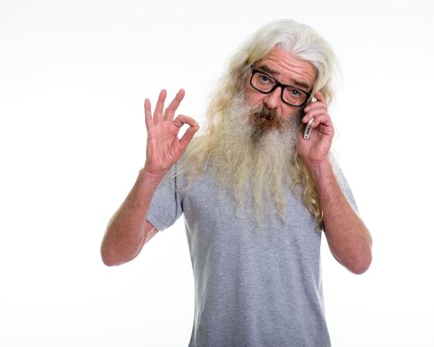 Senior bebaarde man ok teken geven tijdens het gesprek aan de telefoon