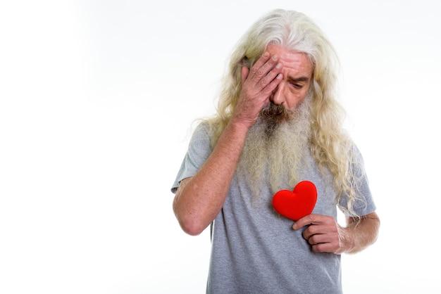 Senior bebaarde man op zoek verdrietig terwijl rode roos