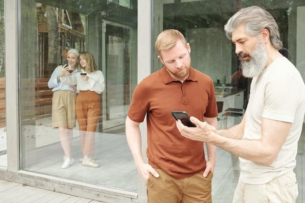 Senior bebaarde man volwassen zoon vragen over smartphone-app terwijl ze praten over technologie in cottage house