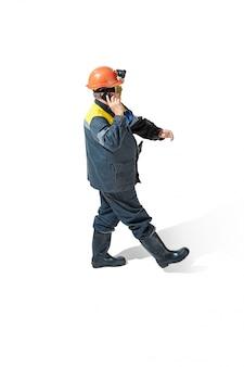 Senior bebaarde mannelijke mijnwerker staande op de camera op een wit