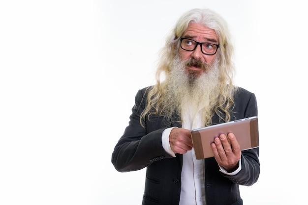 Senior bebaarde zakenman met behulp van digitale tablet