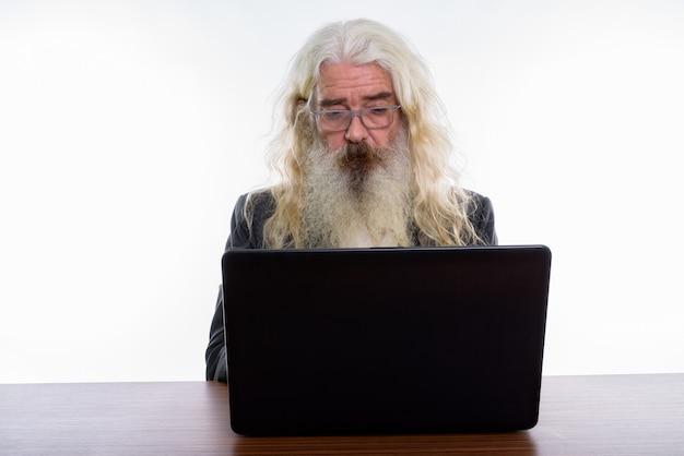 Senior bebaarde zakenman met laptop op houten tafel