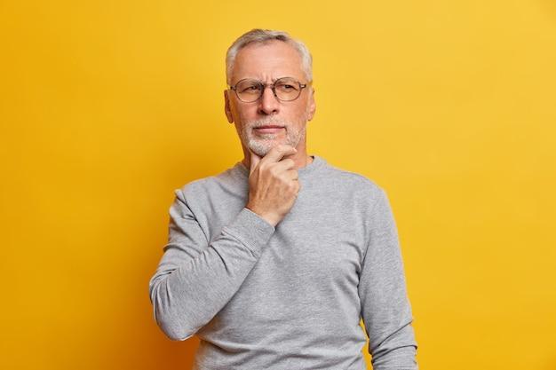 Senior bedachtzame man houdt kin vast en kijkt peinzend opzij, maakt plannen draagt bril en casual grijze trui geïsoleerd over levendige gele muur
