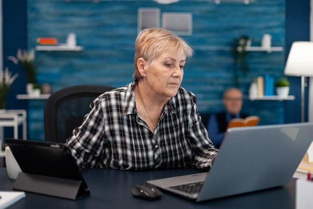 Senior bedrijfseigenaar werkt vanuit kantoor aan huis met behulp van draagbare computer oudere vrouw in huis wonen ...