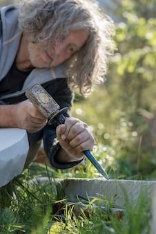 Senior beeldhouwer beeldhouwen met beitel en hamer in steen buitenshuis.
