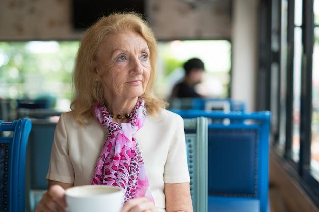 Senior bejaarde vrouw koffie drinken en kijken uit raam