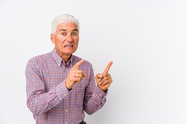 Senior blanke man geïsoleerd geschokt wijzend met wijsvingers naar een kopie ruimte.