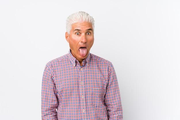 Senior blanke man geïsoleerd grappig en vriendelijk tong uitsteekt.