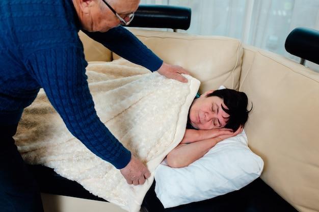 Senior blanke man helpt zijn vrouw om naar bed te gaan en bedekt haar thuis met een deken op de...