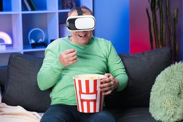 Senior blanke man met een doos popcorn in zijn hand kijken naar video met behulp van virtual reality headset zittend op de bank eten popcorn in de kamer.