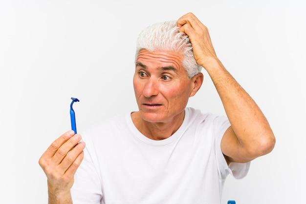Senior blanke man met een geïsoleerd scheermesje geschokt, ze heeft een belangrijke ontmoeting onthouden.