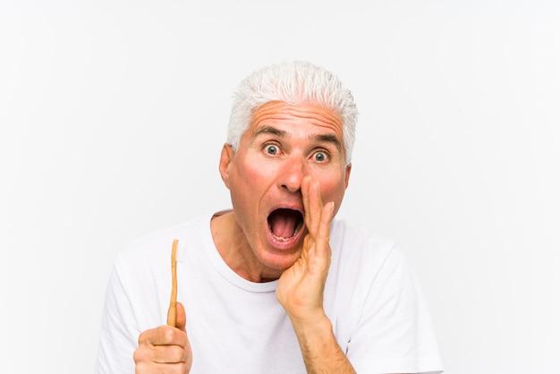 Senior blanke man met een tandenborstel geïsoleerd schreeuwen opgewonden aan de voorkant.