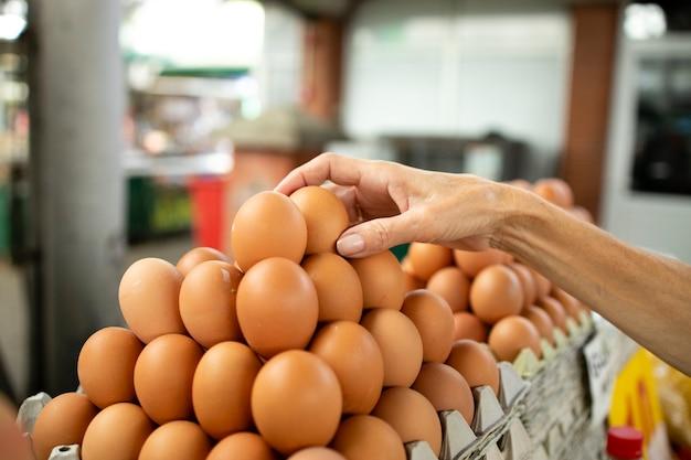 Senior blanke vrouw die kippeneieren koopt op de markt.