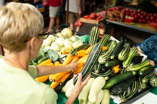 Senior blanke vrouw die pompoen koopt op de markt en een tas vol met gezond voedsel vasthoudt.