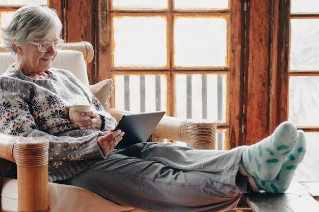 Senior blanke vrouw die thuis ontspant op een leunstoel die een tablet leest met een kopje thee, een warme trui en een bril draagt. comfortabele woonkamer, houten raam