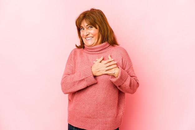 Senior blanke vrouw geïsoleerd heeft vriendelijke uitdrukking, handpalm tegen borst te drukken. liefde concept.