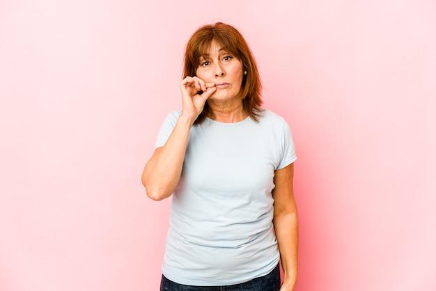 Senior blanke vrouw geïsoleerd met vingers op lippen die een geheim houden.