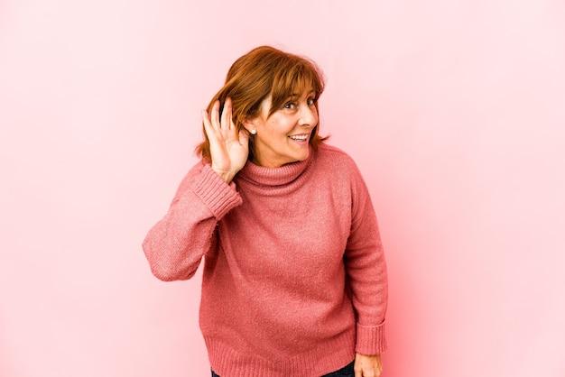 Senior blanke vrouw geïsoleerd proberen te luisteren een roddel.