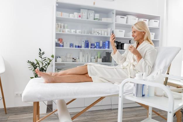 Senior blanke vrouw glimlachend in witte badjas, praten op mobiele telefoon en thee drinken in schoonheidssalon.
