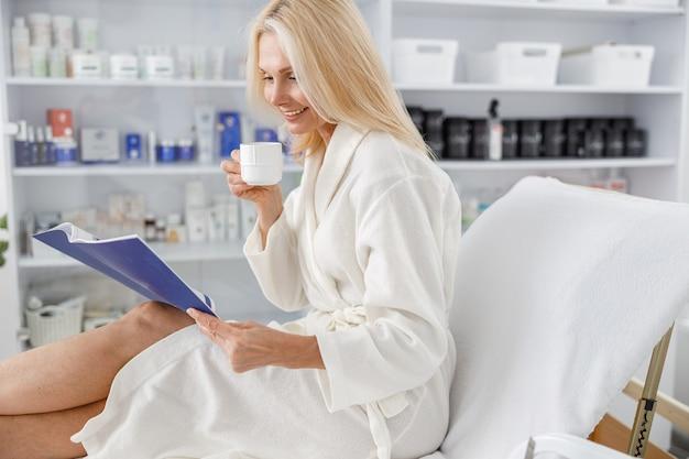 Senior blanke vrouw glimlachend in witte badjas, thee vasthoudend en brochure lezend in schoonheidssalon.