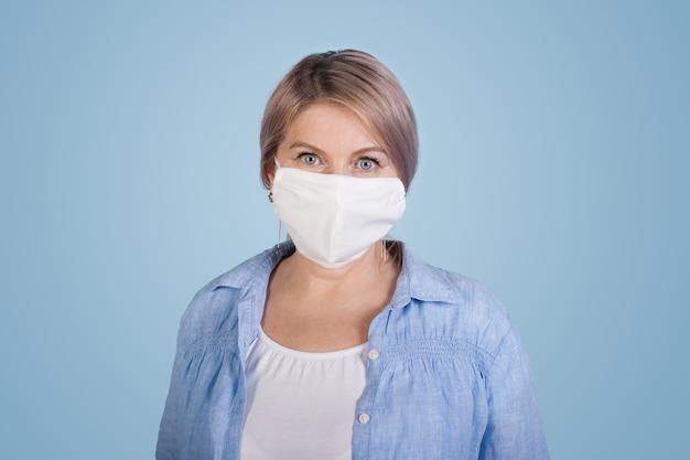 Senior blanke vrouw in wit t-shirt en shirt poseren op een blauwe muur met een medisch masker op het gezicht