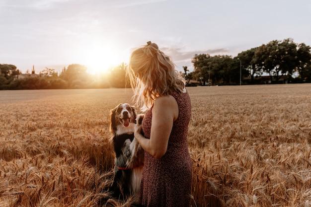 Senior blanke vrouw spelen met border collie hond op tarweveld. vriendschap concept
