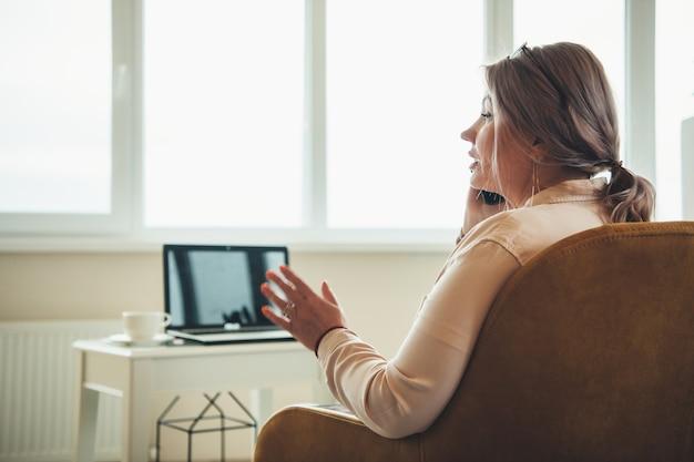 Senior blanke zakenvrouw praten over de telefoon zittend in een stoel met een laptop vooraan
