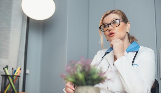 Senior blonde arts met medische hulpmiddelen spreekt tijdens een consult met de patiënt