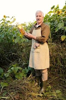 Senior boer in schort en shirt kijkt naar een fles zonnebloemolie in zijn handen terwijl hij tussen grote bloemen voor de camera staat