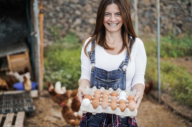Senior boer vrouw oppakken van biologische eieren in het kippenhok - focus op gezicht