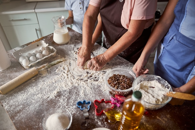 Senior dame bereidt deeg voor bakken met haar kinderen