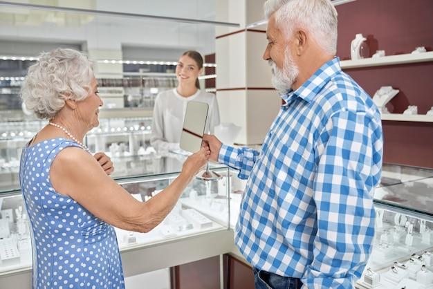 Senior dame in blauwe polka dot jurk probeert op parel ketting