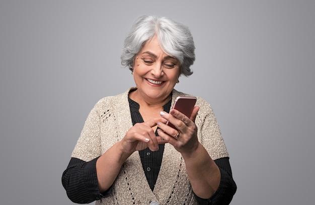 Senior dame lachen met smartphone