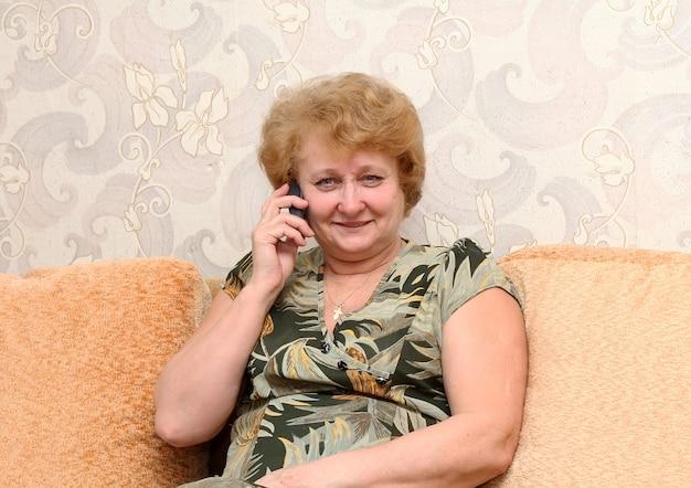 Senior dame spreekt door een mobiele telefoon.