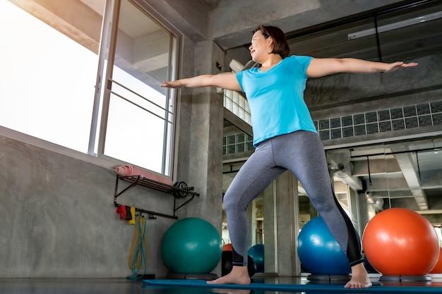 Senior dikke vrouw aziatische doet yoga oefening op fitness gym.