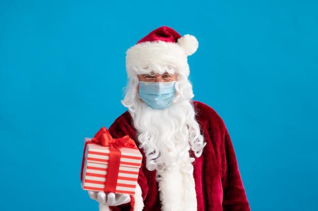 Senior draagt santa claus-kostuum en beschermend masker. man met geschenkdoos. kerstvakantie tijdens pandemisch coronavirus covid 19-concept