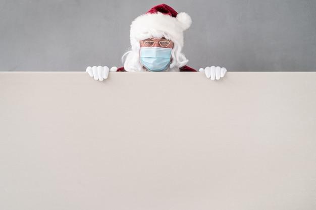 Senior draagt santa claus-kostuum en beschermend masker. man met leeg leeg bord. kerstvakantie tijdens pandemisch coronavirus covid 19-concept