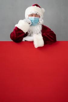 Senior draagt santa claus-kostuum en beschermend masker. man met rode leeg leeg bord. kerstvakantie tijdens pandemisch coronavirus covid 19-concept