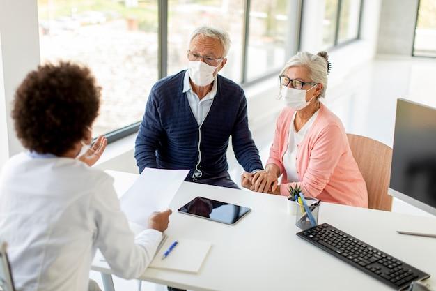 Senior echtpaar met beschermende gezichtsmaskers ontvangt nieuws van een zwarte vrouwelijke arts op kantoor