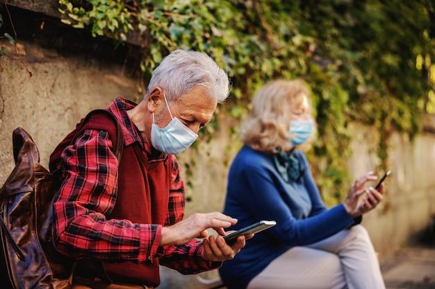 Senior een met beschermend masker op buiten op de bank zitten en mobiele telefoon gebruiken. op de voorgrond is senior vrouw die telefoon gebruikt en ook een masker draagt. senioren waarderen sociale afstand.