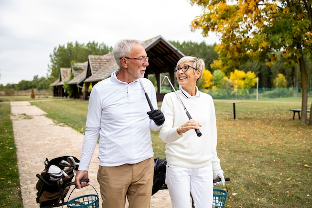 Senior elegante mensen brengen graag hun vrije tijd door met hun pensioen door golfspel te spelen.