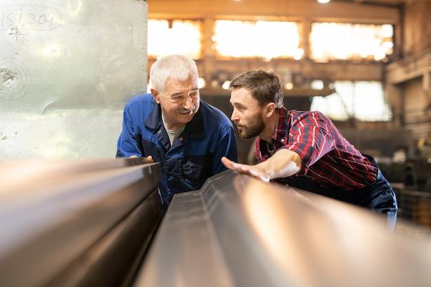 Senior en jonge ingenieurs in werkkleding advies over kenmerken van metalen werkstuk voor industriële machine